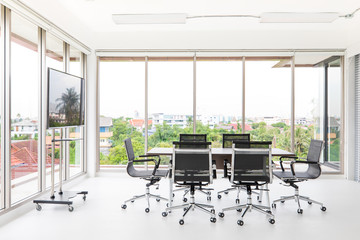Group of conference table and chairs in white and wide office with television screen.