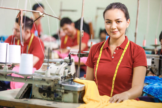 Seamstress in textile factory smiling while  sewing with industr