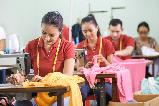 asian workers in garment factory sewing with industrial sewing m