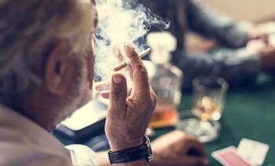 A man smoking in a gambling circle