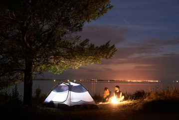 Young couple, bearded man and woman hikers having a rest at night camping on sea shore, lit by burning campfire at tourist tent under big tree on quiet water surface background. Tourism concept
