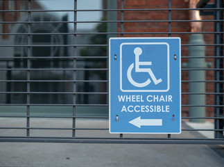 Handicap sign, wheel chair accessible logo pointing to left outdoor