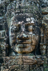 Stone face of Buddha on the tower of the ancient temple of Angkor Tom in Cambodia.