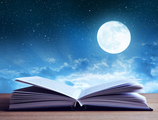 Open book on wooden plank night sky with moon in the background.