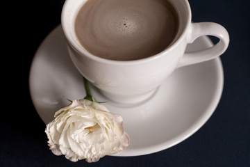black coffee with milk in a white mug with a saucer