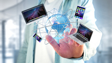 Businessman holding a Computer and devices displayed on a futuristic interface with international network  - 3d render