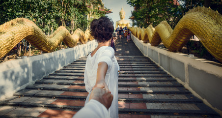 On the way to the Big Buddha. Thailand, Pattaya. The girl is holding the guy by the hand. Follow me.