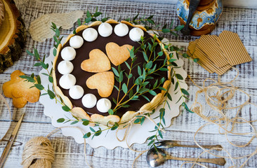 Cheesecake with gingerbread cookies on wood with greenery decoration