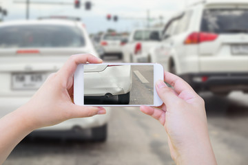 Hand using mobile smart phone taking photo of the car crash accident damage for insurance