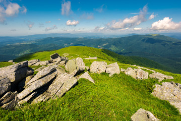 boulders down the grassy slope of a hill. beautiful sky over the distant mountains. stunning summer weather