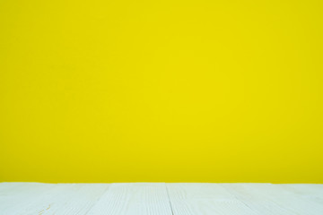 Empty white wooden table with yellow wall background