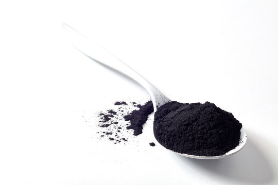 Spoon of round activated black plant charcoal