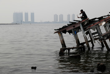 A youth stands on the wreckage of a wooden boat, during fishing with a slingshot, as smog covers North Jakarta