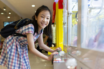 Asian girl playing Claw Game or cabinet catches the doll at one of the shopping mall outlets