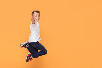 Little boy jumping in the studio, smiling.