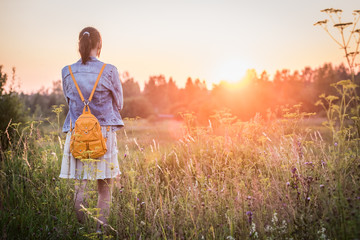 Young girl in a dress and with a backpack in the nature at sunset, rear view