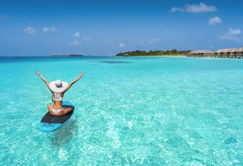 Glückliche Frau auf einen Surfbrett treibt über den türkisen Gewässern der Malediven und genießt ihren Sommerurlaub