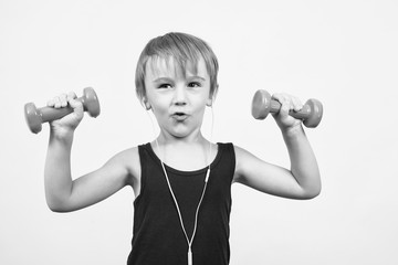 Little boy training with dumbbells. Happy child goes in for sports. Healthy and sporty lifestyle concept. Sporty childhood. Funny kid with dumbbells, listens to music through headphones.