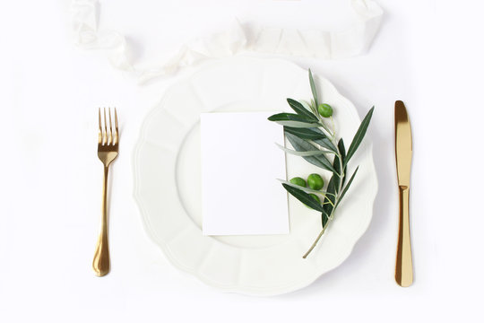 Festive table summer setting with golden cutlery, olive branch, porcelain dinner plate and silk ribbon on white table background. Blank card mockup. Mediterranean wedding or restaurant menu concept