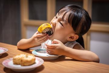 Asian little Chinese girl eating rice balls