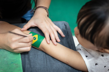 Asian little Chinese girl getting her arm painted a Brazil Flag