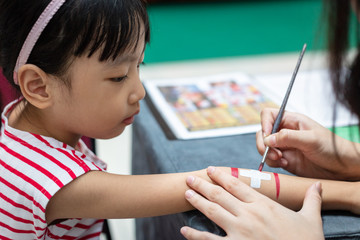 Asian little Chinese girl getting her arm painted a Swiss Flag