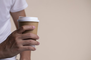 Hand holding a paper cup of coffee.
