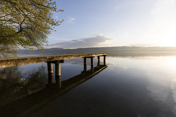 Wonderful morning mood on Lake Sempach in Switzerland. A wooden walkway leads out onto the lake.