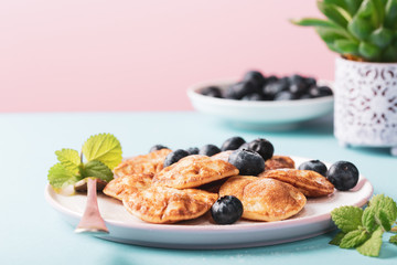 Dutch mini pancakes called poffertjes with blueberries, sprinkled with powdered sugar. Healthy food concept with copy space.