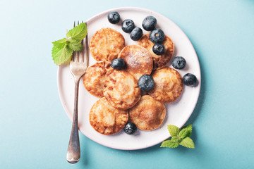 Overhead shoot of dutch mini pancakes called poffertjes with blueberries, sprinkled with powdered sugar. Healthy food concept with copy space.