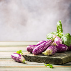 Heap of small eggplant or aubergine vegetable with basil leaves on old wooden background. Healthy food concept with copy space.