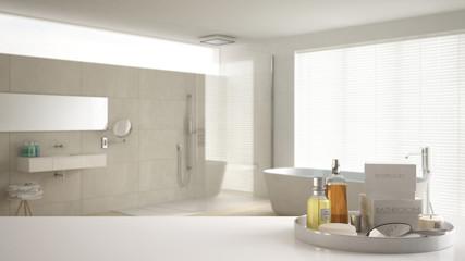 Spa, hotel bathroom concept. White table top or shelf with bathing accessories, toiletries, over blurred cream minimalist bathroom, modern architecture interior design