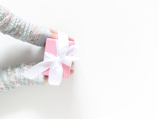 Female hands holding pink gift box, on white wooden background. Festive background. Birthday, Valentines day, Christmas, New Year. Flat lay, top view, copy space