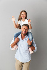 Photo of joyful family smiling at camera while little girl having fun and sitting on the neck of her happy father, isolated over gray background