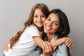 Photo of attractive woman with little daughter smiling and hugging together, isolated over gray background