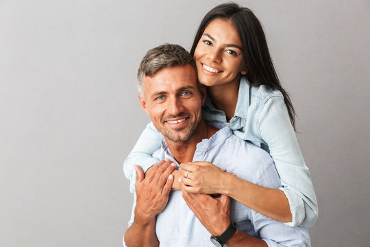 Portrait of beautiful couple man and woman in basic clothing smiling and hugging together, isolated over gray background