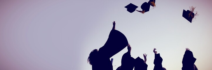 Five graduates throwing their hats