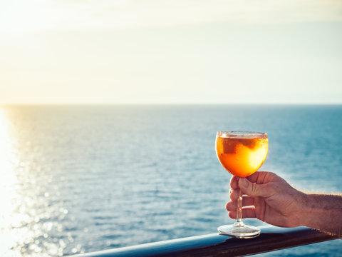 Male hand with a glass of beautiful pink cocktail on an open deck of a cruise ship on a background of sunset, sea waves and clear sky