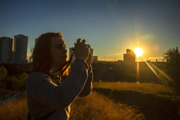 A young man is photographing something on the background of the setting sun