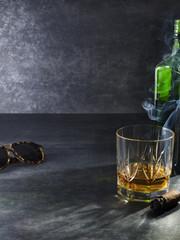 Glass of liquor with smoking cigar