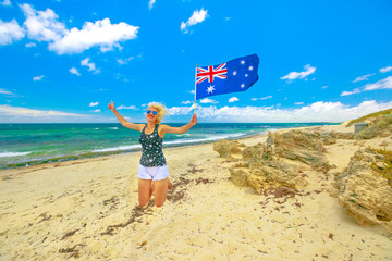 Happy woman jumping on white beach waving Australian Flag. Blonde girl happiness jump in Mettams Pool, Trigg Beach, North Beach neighborhood near Perth, Western Australia. Tourism in Oceania.