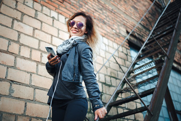 Smiling young woman in sunglasses, a black leather jacket, black jeans standing on an urban metal stair against a brick wall and dances. Woman listening to music on the stairs of industrial building.