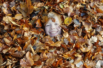 Girl playing with leaves in autumn