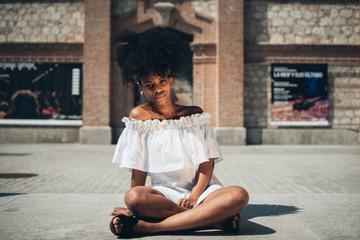 Trendy black woman sitting on street