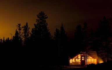 Illuminated wall tent, cabin, camp fire, bonfire, silhouette of pine trees, near Whitehorse, Yukon Territory, Canada, North America