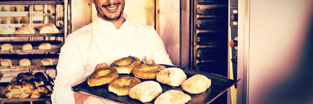 Happy baker showing tray of fresh bread