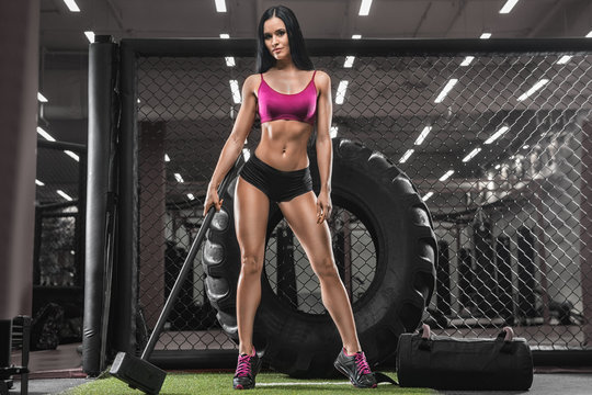 A young sexy brunette, an athlete bodybuilder, in a modern gym, doing cross-fit exercises. Sledge wheel. Concept - strength, crossfit, sports nutrition, diet.