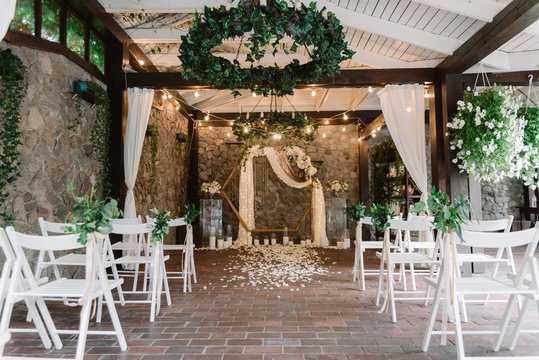 Magnificent decoration of a wedding ceremony with original details and candles. Hexagonal archway.