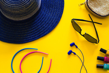 Women's leisure accessories including wide brimmed blue hat. Flat lay design on yellow.
