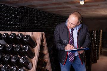 Winemaker with clipboard in wine cellar